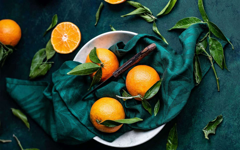 tangerine oranges sit in decorative bowl